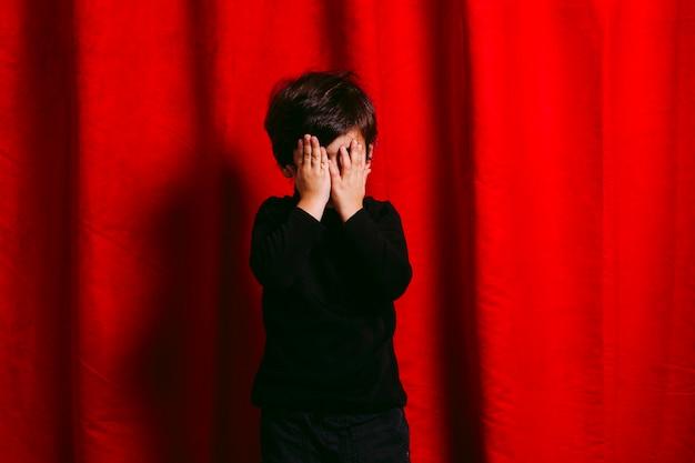 Menino de três anos, vestindo roupas pretas, cobrindo o rosto, contra uma cortina vermelha