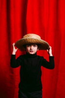 Menino de três anos, vestindo roupas pretas, feliz com sua cabana de palha