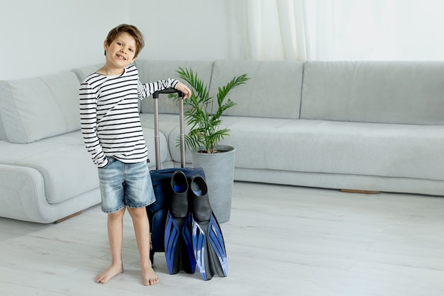 Menino de turista com uma mala e nadadeiras fica em casa