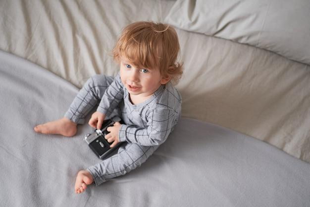Menino de um ano brincando na cama com uma câmera velha, foto de estilo de vida