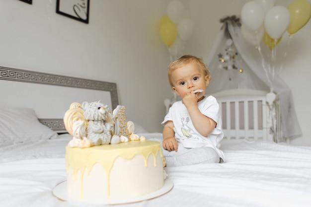 Menino de um ano de idade, degustação de um bolo de férias em seu aniversário