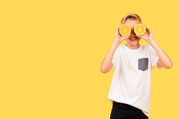 Menino de vista frontal, cobrindo os olhos com fatias de laranja