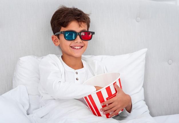 Menino de vista frontal com óculos 3d e comendo pipoca