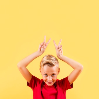 Menino de vista frontal com sinal de paz acima da cabeça