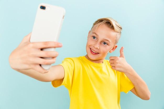 Menino de vista frontal com sinal ok posar para selfie