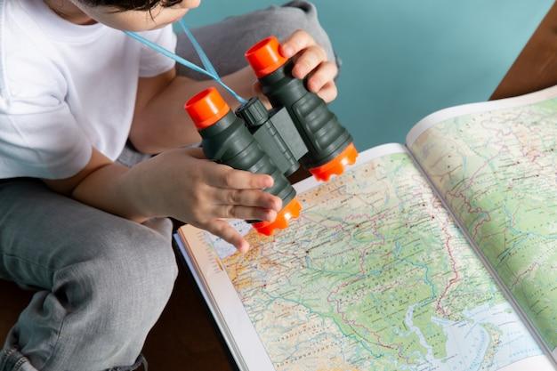 Menino de vista frontal, olhando através do mapa com binóculos