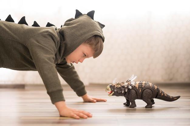 Menino de vista lateral em traje de dinossauro
