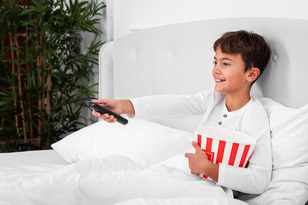 Menino de vista lateral na cama com controle remoto e pipoca