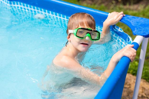 Menino debaixo d'água em uma máscara. uma criança nada na piscina. um menino nos copos de água na água.