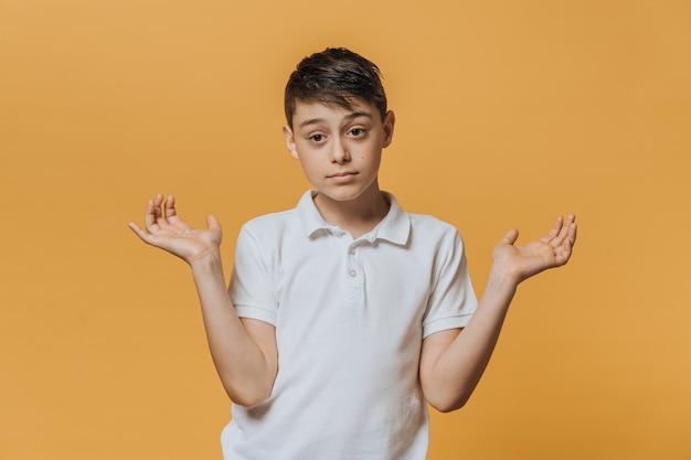 Menino desapontado em uma camiseta branca abre as mãos em clima de dúvida. emoções de pessoas sinceras.