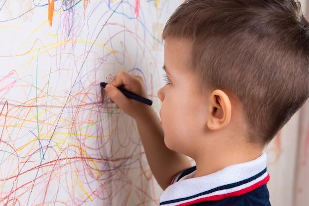 Menino desenha na parede com giz colorido. a criança está envolvida na criatividade em casa