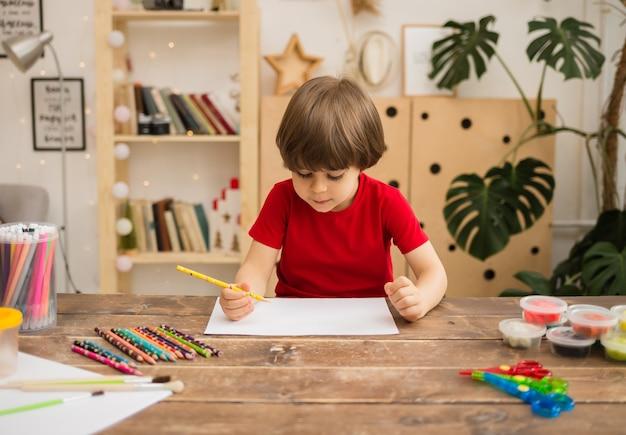 Menino desenhando com um lápis em papel branco em uma mesa de madeira com papelaria