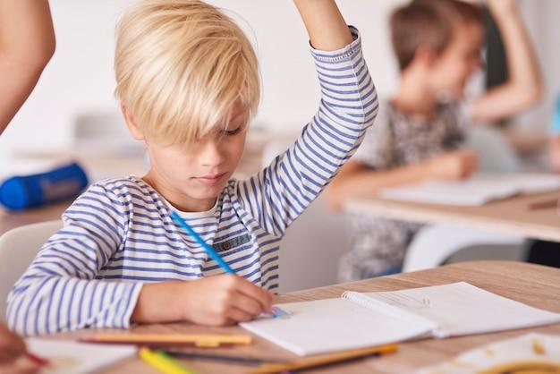 Menino desenhando e levantando a mão