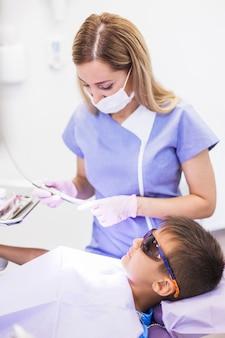 Menino, desgastar, segurança, protetor, óculos, inclinar-se, cadeira dental, frente, odontólogo