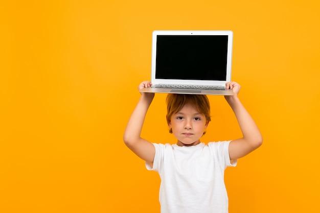 Menino detém um laptop na cabeça em uma parede amarela com espaço de cópia