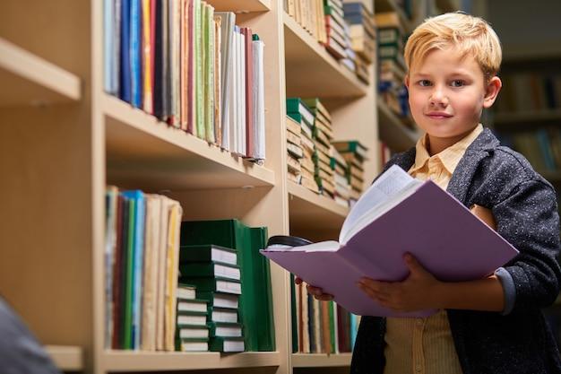 Menino diligente com o livro entre as estantes na biblioteca do campus, ele está olhando para a câmera. aprendizagem, cérebro, conceito de educação