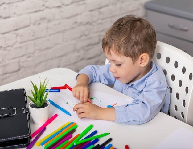 Menino do ensino fundamental aprendendo em casa, criança alegre e fofa, desenho