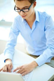 Menino do estudante com um laptop