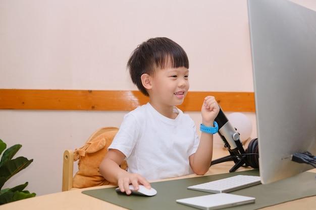 Menino do jardim de infância estudando online, frequentando a escola via elearning criança em casa ensino à distância