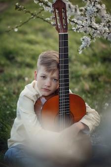 Menino do retrato com a guitarra que senta-se na grama no dia de verão.