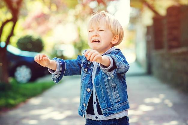 Menino doce criança loira chorando ao ar livre. filhinho puxa as alças para a mãe.