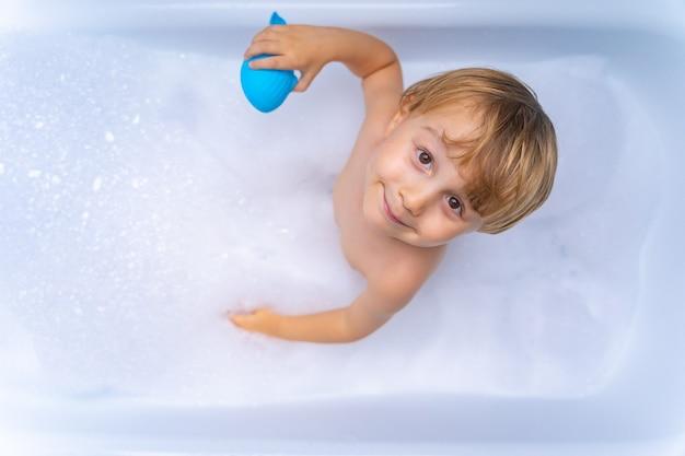 Menino doce e loiro brincando com um brinquedo tomando banho na banheira