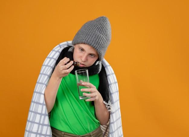Menino doente com chapéu e lenço quente enrolado em um cobertor, pingando gotas de um frasco de remédio em um copo em cima da parede laranja