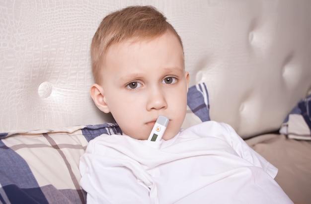 Menino doente com termômetro digital. menino doente mede a temperatura do corpo e não se sente bem