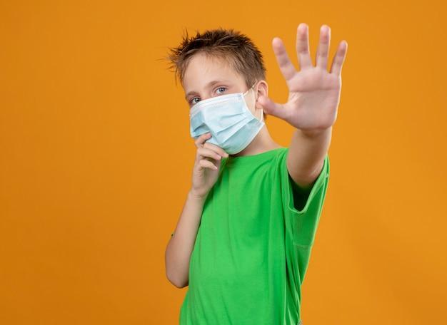 Menino doente com uma camiseta verde e máscara protetora facial fazendo gesto de parada com a mão em pé sobre a parede laranja