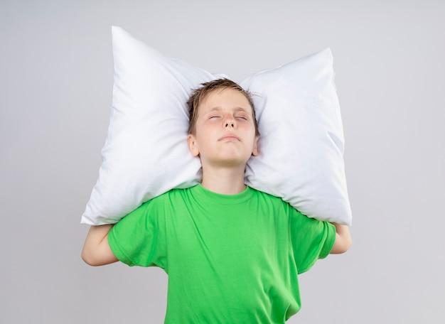 Menino doente com uma camiseta verde se sentindo mal, segurando um travesseiro com os olhos fechados, parado sobre uma parede branca