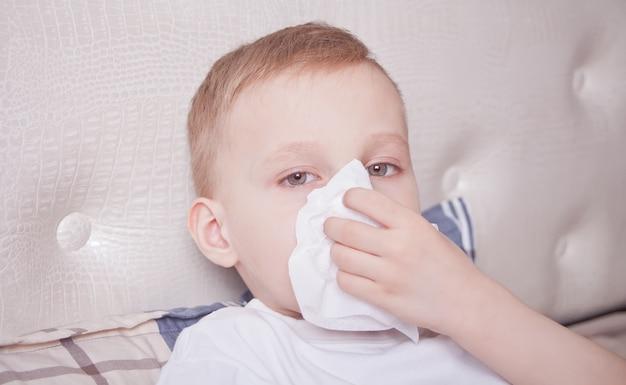 Menino doente, deitado em uma cama e assoar o nariz