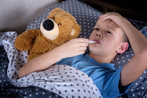 Menino doente deitado na cama com termômetro na boca ao lado do brinquedo
