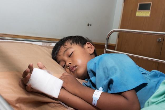 Menino doente no hospital com solução salina intravenosa