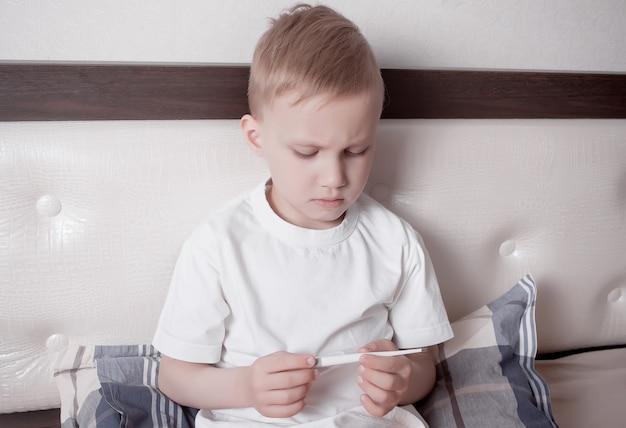Menino doente que senta-se na cama e que olha o termômetro digital.