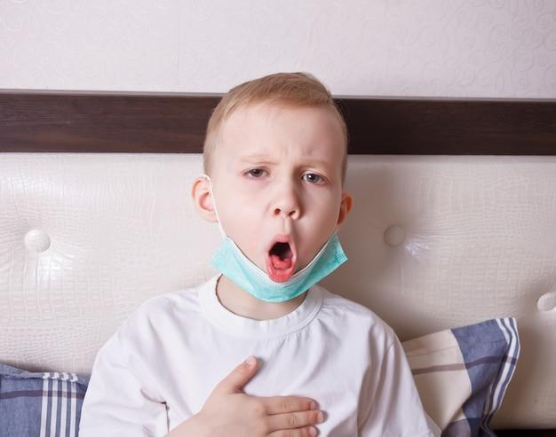Menino doente que sofre de tosse na cama em casa