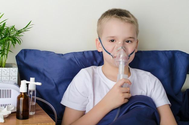 Menino doente, respirando através do nebulizador
