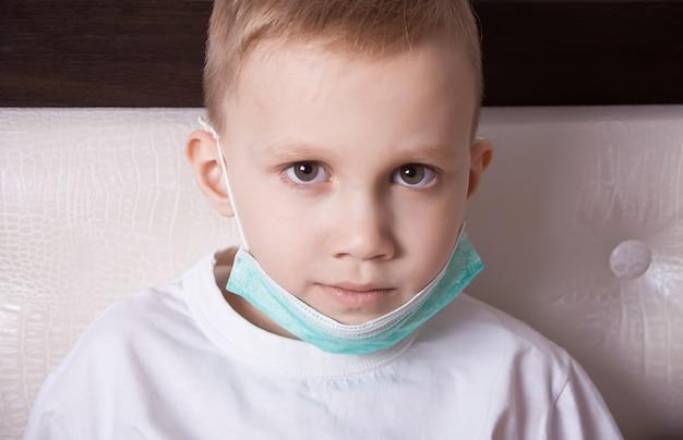 Menino doente, sentado na cama com máscara médica e não se sente bem