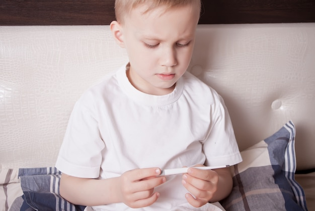 Menino doente, sentado na cama e olhando para o termômetro digital. menino doente mede a temperatura do corpo e não se sente bem
