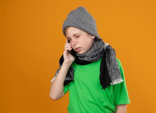 Menino doente, vestindo uma camiseta verde com um cachecol quente e um chapéu, sentindo-se mal, falando no celular, em pé sobre a parede laranja