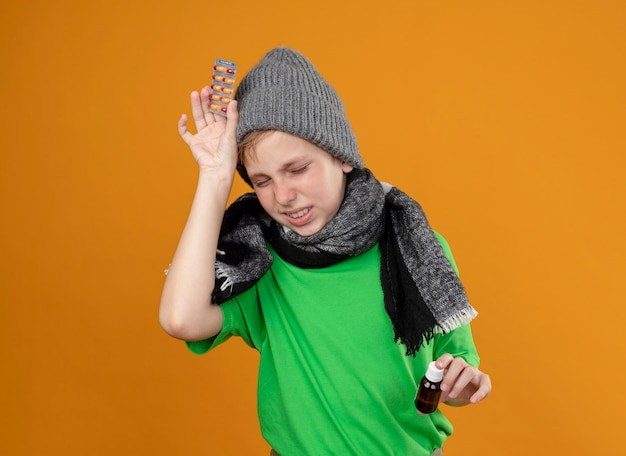 Menino doente, vestindo uma camiseta verde com um lenço quente e um chapéu, sentindo-se mal, segurando um frasco de remédio e pílulas, sofrendo de dor de cabeça, doente e infeliz em pé sobre a parede laranja