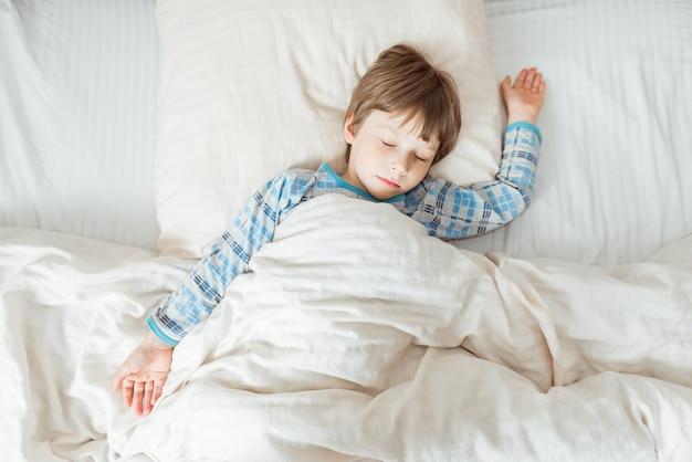 Menino dormindo em sua cama branca. vista do topo