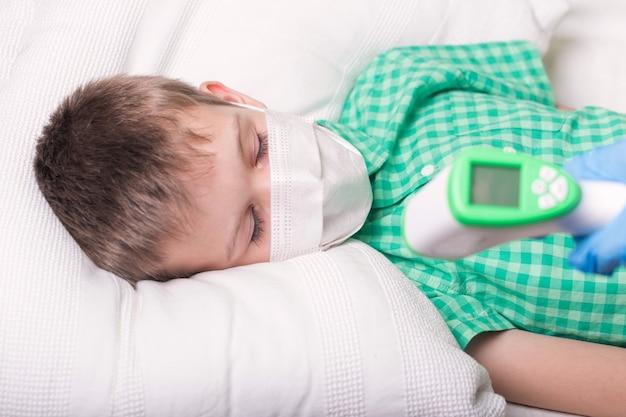 Menino dormindo mede a temperatura com um termômetro