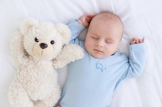 Menino dormindo na cama deitado de costas com um urso de pelúcia de pijama azul