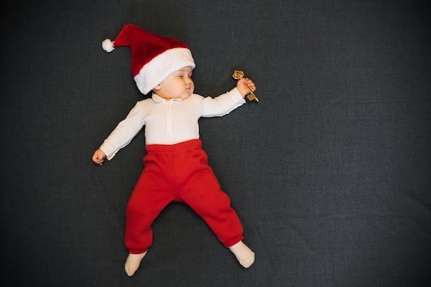 Menino dormindo no chapéu de papai noel encontra-se com uma chave na mão