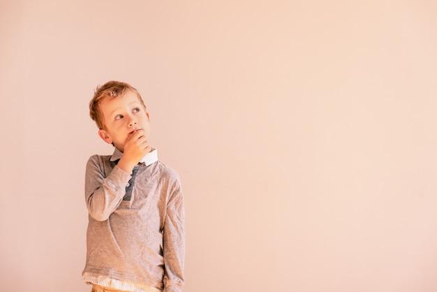 Menino dos anos de idade 5 com gesto pensativo muito expressivo, no fundo branco com área de espaço da cópia.