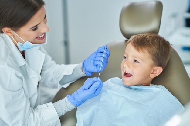 Menino e dentista no consultório do dentista