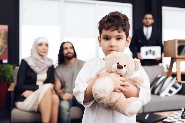 Menino é detém o ursinho de pelúcia. os pais estão olhando no filho.