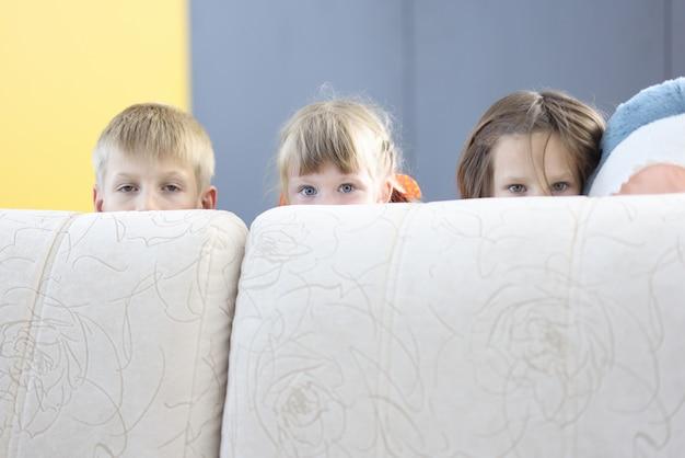 Menino e duas meninas se escondem atrás do sofá e olham para fora.