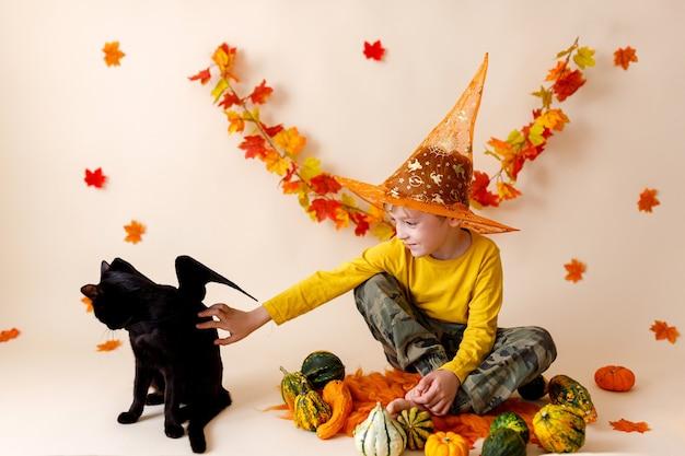 Menino e gato preto com lanterna de abóbora. dia das bruxas.
