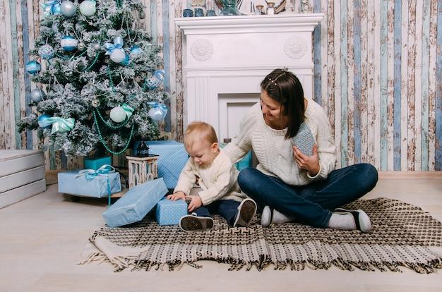 Menino e mãe brincando com presentes de natal perto da árvore do ano novo